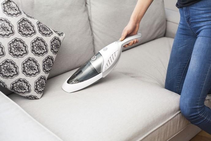 ハンディクリーナーでソファを掃除する女性