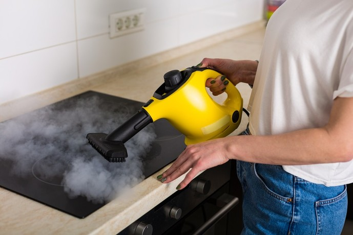 キッチンの油汚れを高温スチームクリーナーで掃除する人