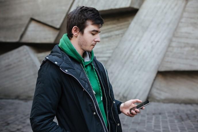 緑パーカーと黒コートのメンズコーディネート