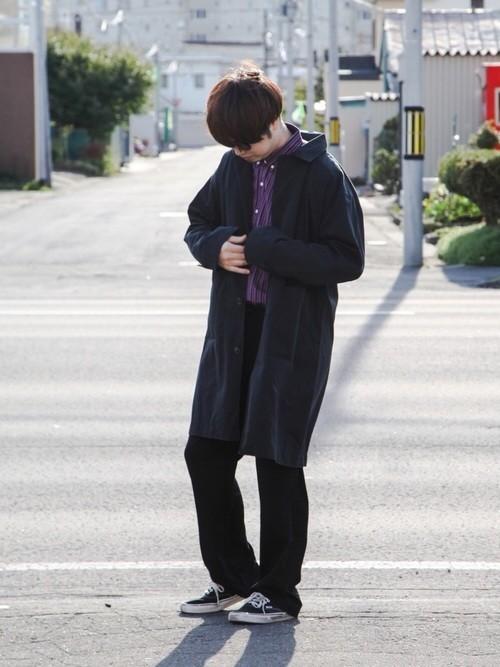 黒ステンカラーコートと黒パンツのコーデに黒スニーカーを合わせたメンズコーディネート