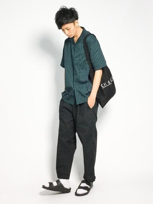 緑ストライプシャツと黒パンツのメンズコーディネート