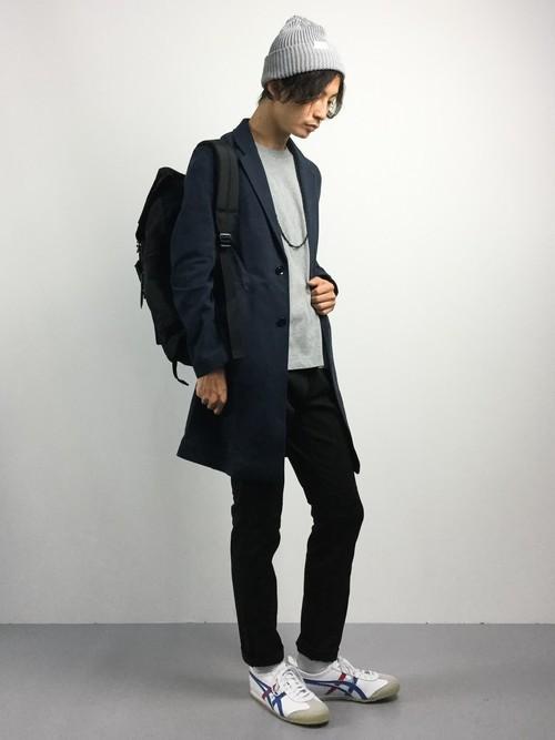 黒チェスターコートと黒パンツのコーデに白スニーカーを合わせた着こなし
