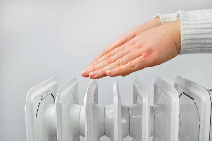 オイルヒーターで手を温める人