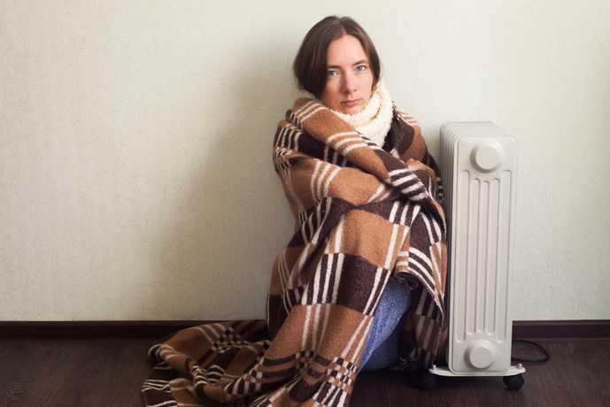 オイルヒーターで体を温める女性