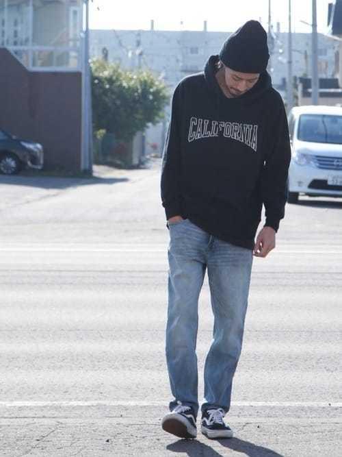 黒パーカーとデニムパンツのコーデに黒ニット帽を合わせた着こなし