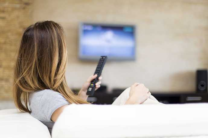壁掛けテレビでドラマを楽しむ女性