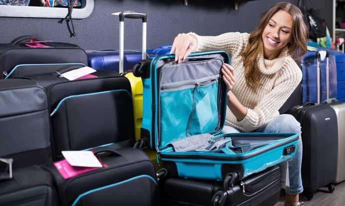 安いスーツケースを開く女性