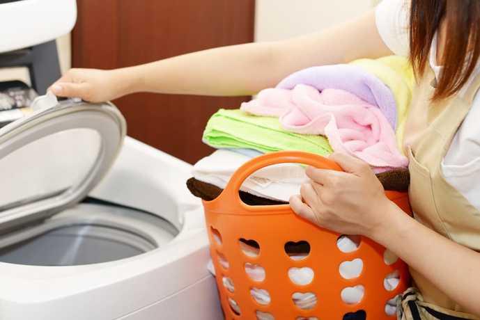 縦型洗濯機で洗濯物を洗った女性