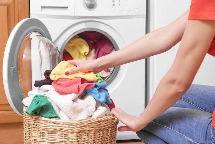 乾燥機付きの洗濯機で衣類を洗う人