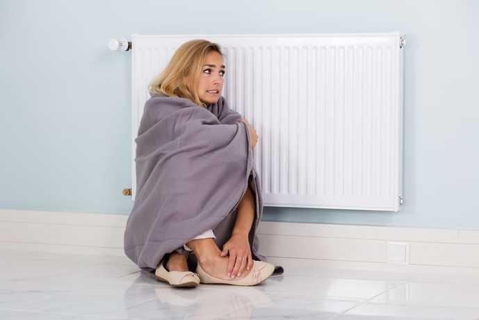パネルヒーターで温まっている女性