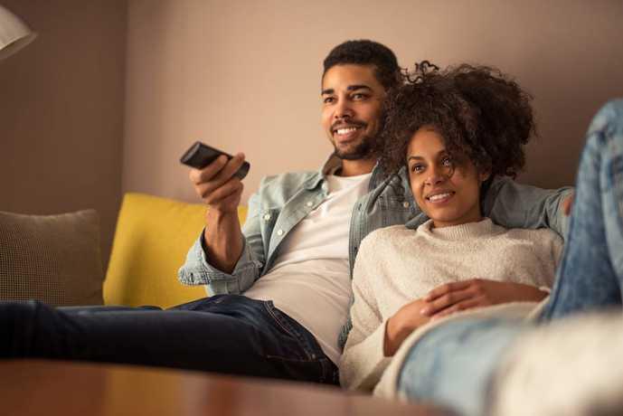 55インチのテレビで映画を楽しむカップル
