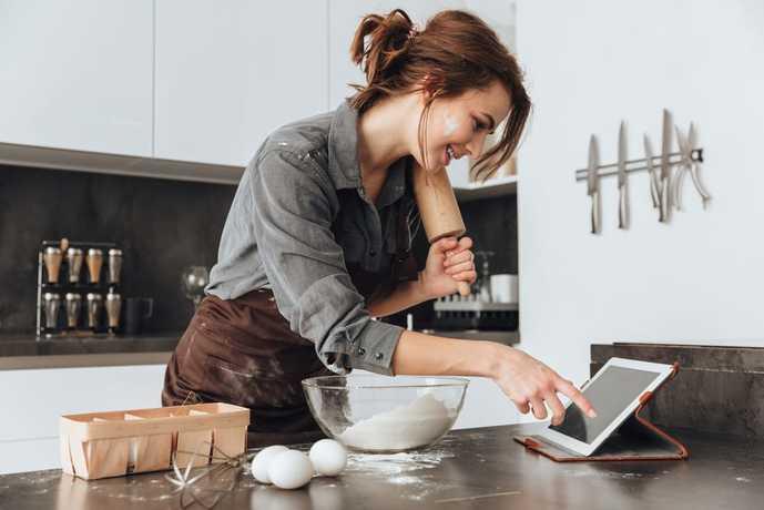 キッチンで防水用タブレットを使っている女性