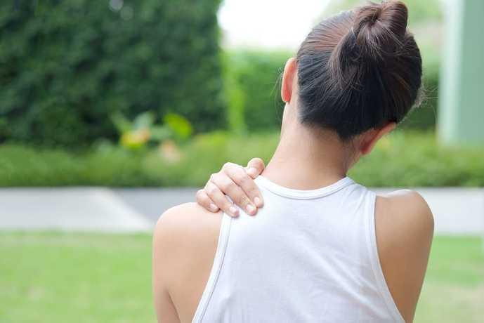 肩甲挙筋の場所を触っている女性