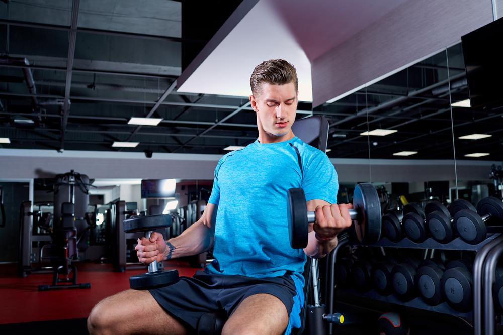インクラインダンベルカールで体を鍛えいてる男性