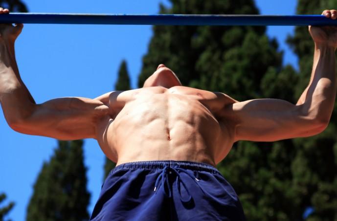 ワイドグリップチンニングを加重した上体で行う男性