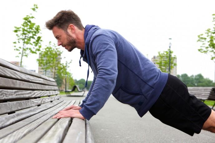 インクラインプッシュアップをベンチで行っている男